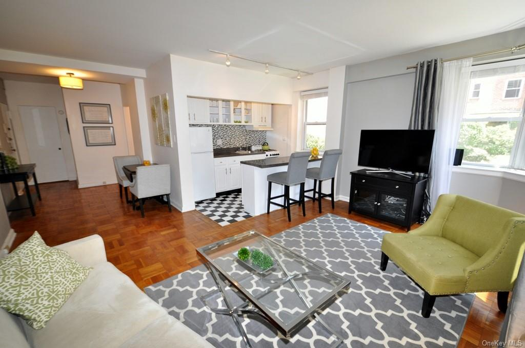 The bright and sunny living room has western and southern exposures and parquet floors.  A breakfast island separates the kitchen while keeping the open concept.