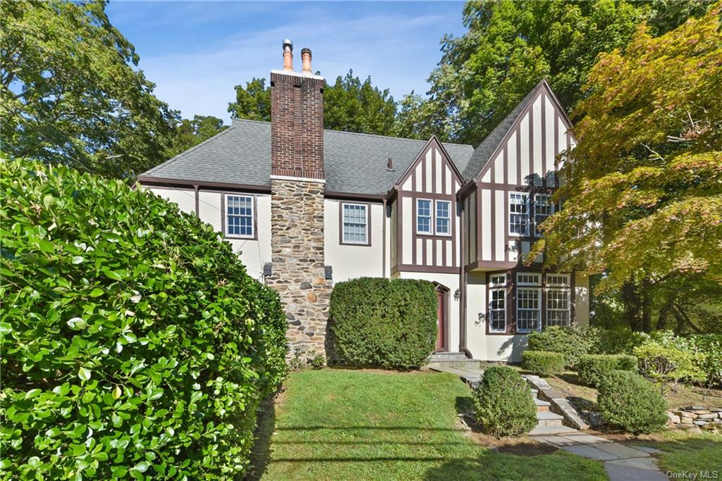 Charm abounds in this sun filled Scarsdale Tudor on oversized level lot within steps to elementary school. A welcoming center hall leads to classic layout that offers ideal living space including a gracious living room with gas fireplace, new powder room, sun room/office with oversized windows and French doors to private rear patio. The dining room has beautiful custom built ins that lead into kitchen and mudroom area that leads to attached garage. The 2nd floor boasts a large primary bedroom with an en-suite bath and walk in closet, plus 2 additional bedrooms and a hall bath. On the 3rd floor, there is a bedroom and large bathroom.  Hardwood floors and updated windows throughout. The private backyard & side yard with mature plantings will be the site of endless bbq's and outdoor fun. Enjoy suburban living at its finest with a remarkably convenient location close to schools, train, shops, restaurants & more!