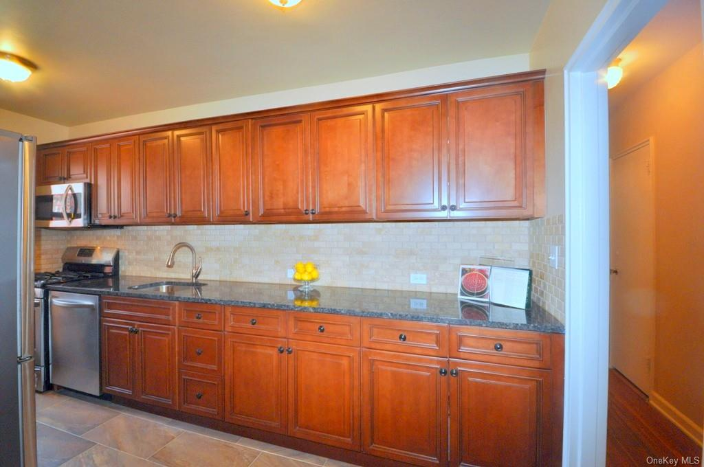 New Kitchen with over 15 ft of Granite Counters, Stainless Steel Appliances including a dishwasher, range, microwave, refrigerator, Custom Cherry cabinets with soft self closing draws. An open feel has been created by opening the wall between the kitchen and dining area.