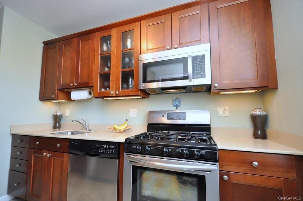 Renovated kitchen with Quartz Counters, Cherry Cabinets and Stainless steel appliances including a dishwasher, range, microwave and refrigerator.