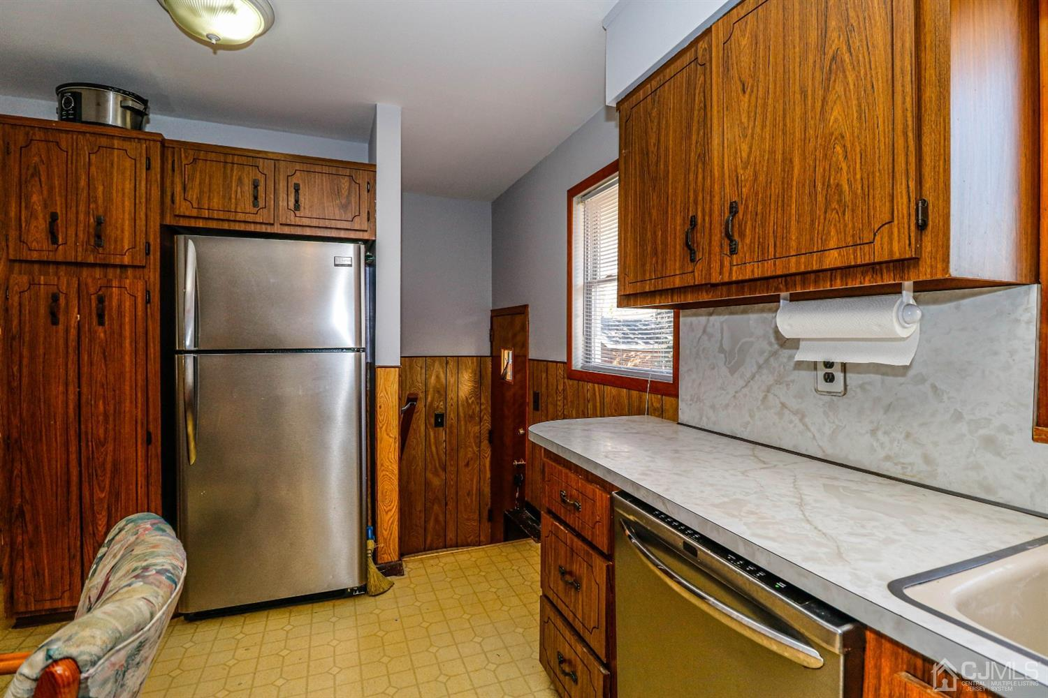 Pantry storage, stainless steel refrigerator and door leading to yard area.