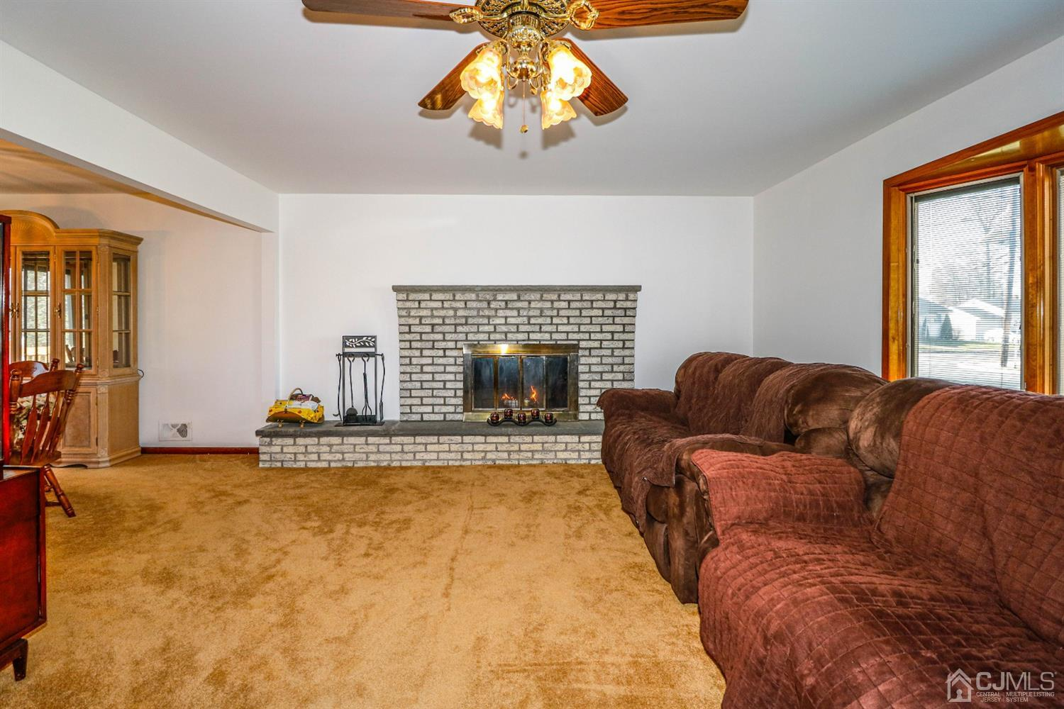 Spectacular Formal Living room with Pella bow window and brick wood burning fireplace.