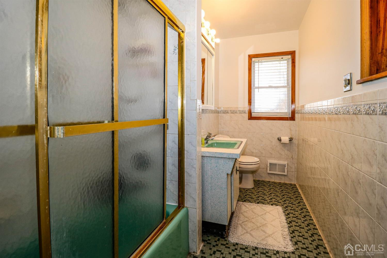 The main bath has tub/shower combination with shower doors, vanity sink and newer commode.