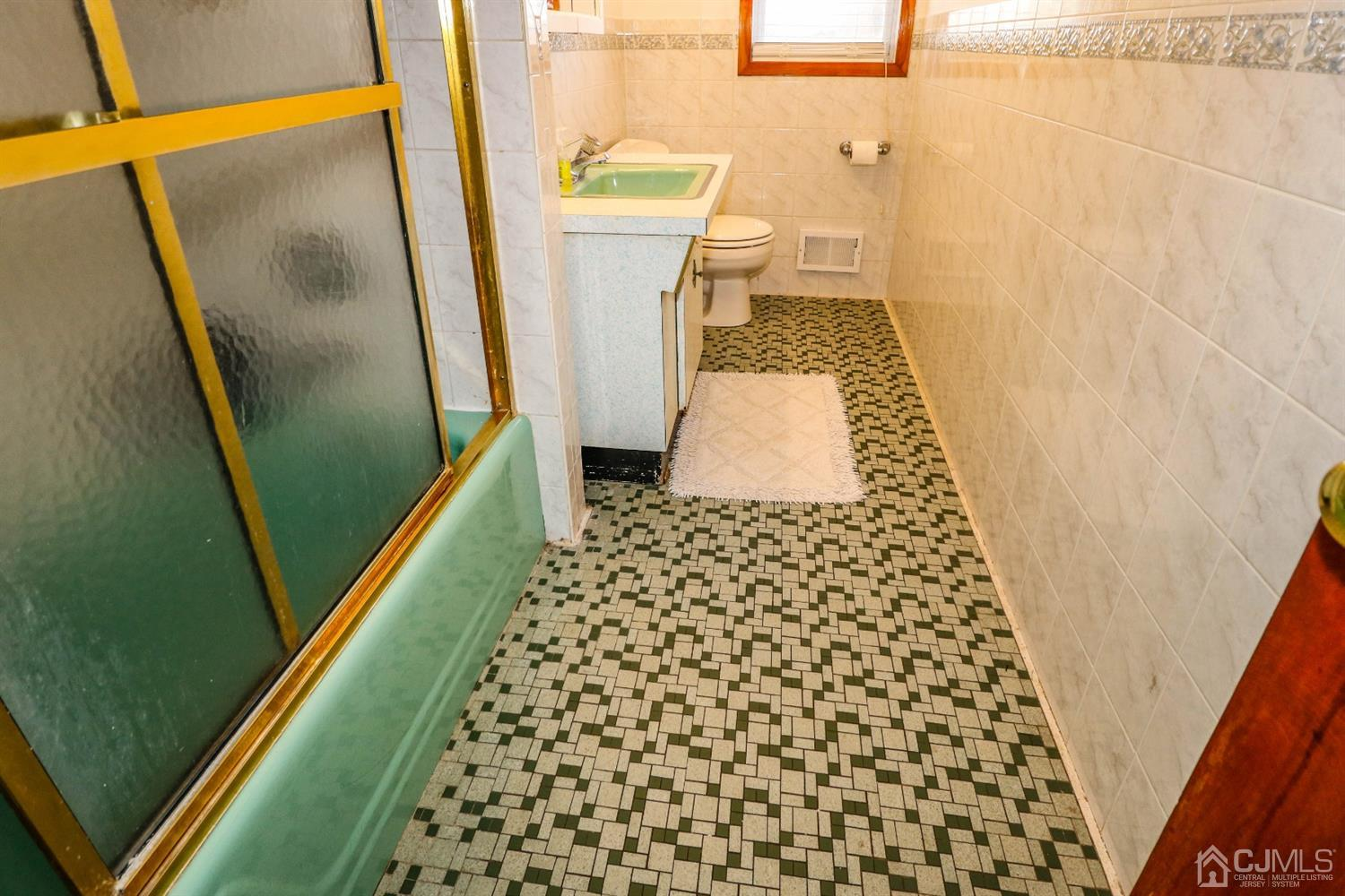 Tiled floors and partially tiled walls in main bath.