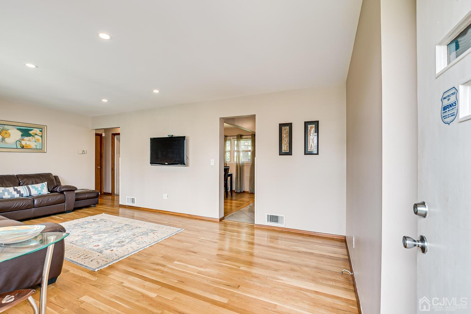 View of the Living Room with Recess lights, Harwood Floors and entrance to Dining Room and Bedrooms.
