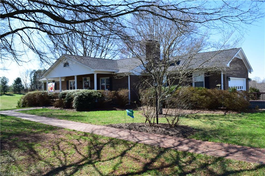 Updated brick home with vinyl trim. Great view of Pilot Mountain. Beautiful hardwoods throughout. Kitchen with granite counter tops and gas cook top. Move in ready home with 3 bedrooms, 3 baths, full finished basement. Gas log fireplace in living room and den.  New heat pump 2013 with gas back up you control. 30 year roof 2011. Nicely finished basement. Large den, sewing room(bedroom), laundry and office. Floored attic storage. 27' X 16' deck for entertaining. Storage building. Mature Yard. Home Warranty.