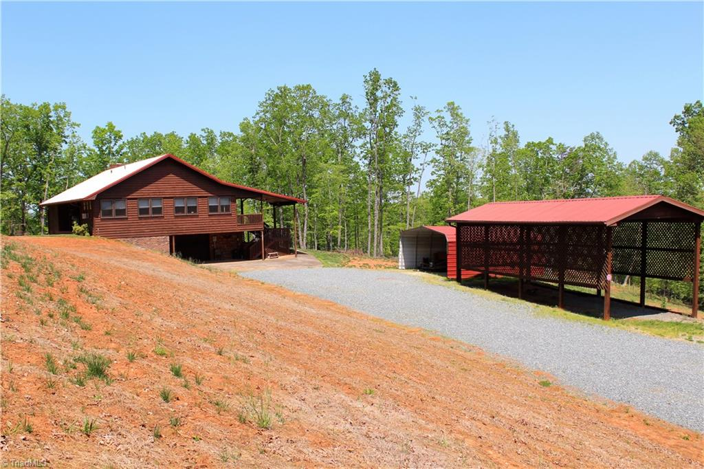 Wonderful mountain home on over 6 acres. Home is cedar sided, has perfect rocking chair front porch for those evenings of relaxing. Also has hardwood floors thru out most of the home, large bedrooms, rock fireplace, rear patio for those cookouts, and an extra large sun room. Home site was recently cleared, leaving trees on back of property.  Home is configured with a full basement workshop, with basement garage, also property has a large rv shelter and 2 car carport.  20 additional acres are available.