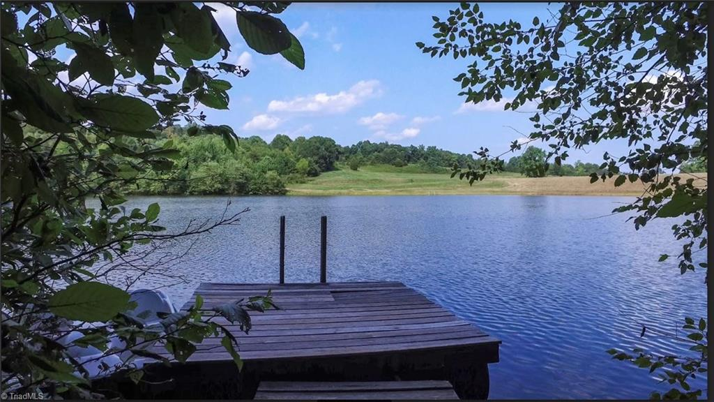 Welcome to your sanctuary on 19 private acres...a peaceful home among the towering trees with a peek of the 10 acre lake through the foliage. The half mile driveway ensures you can leave the cares of the world behind. Home exterior is Cedar and blends into the natural setting. Open floor plan opens to a large deck among the tree tops. A cozy guest cottage is located just steps away. Follow a winding trail to the lake; picnic on viewing platform or take a canoe or kayak from the floating dock.