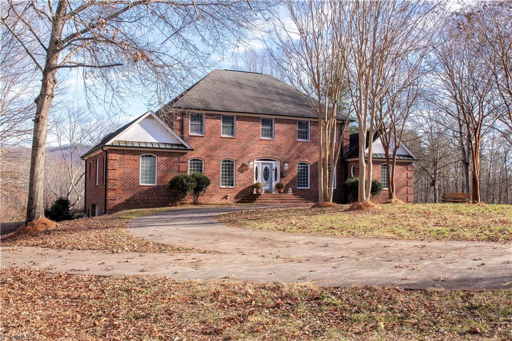 Country Aristocrat's Estate! Private entry into your own 36 acre country estate, spectacular mountain views, in the heart of the Yadkin Valley. Beautiful hardwood floors thru out, 4 car garage, wet bar on main level and large basement game room with bar and plenty of room for entertaining while you shoot a game of pool. Home consists of the option of a main level master or 2nd level master, 4 br/5ba, pond with mountain views both directions, an abundance of wildlife and the option of buying 40 acres more!