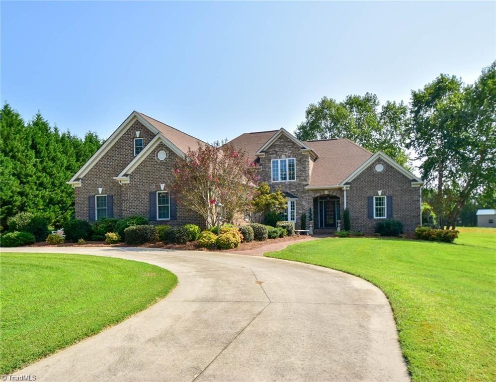 Sellers Motivated!  Brick-precast stone home w/ water-view.  Custom built w/ artist from Old Salem designed front door.  Quartz kitchen countertops / granite bath countertops.  Wood/porcelain tile flooring, two story great room-dining room w/ large heated sun room leads to elegant outdoor backyard living area w/ flagstone patio, built in plumbed sink, jenn-air grill, charcoal grill, firepit.  Master bath w/ oversized shower w/ 3 sep. shower heads.  One owner in immaculate condition/quality.