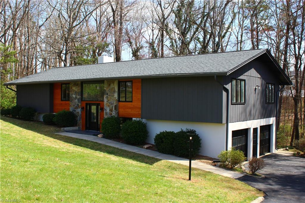 "Come home to this spacious stunner. Ideally located close to 1-40, restaurants, shopping and Tanglewood Park. Stylishly updated with casual elegance, this home will steal your heart. New features include, roof, HVAC, granite counter tops, custom back splash, gorgeous laminate, new carpet, appliances etc. Enclosed sun-porches on upper and lower level, large 1.45 acre lot. Lower level den with bar and fireplace for ""man cave"" space, office, and kitchen area. 2:10 Home Buyers Warranty included!"