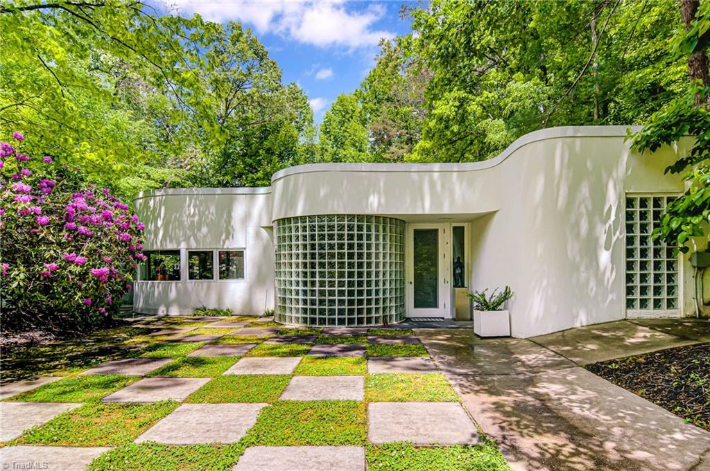 """RECENT 2020 RENOVATIONS INCLUDE ROOF, MBA, HVAC. Desirable leafy """"pocket neighborhood"""" on nearly 2 acs. One-level living with 3250 SF. Ceiling to floor windows, curved glass, skylight, glass block walls, gourmet kit, high-end appliances, MBA total re-dux. 3-car att gar features glass garage doors & catering kitchen; Asian-inspired landscape, 2-level Japanese tea house, greenhouse/4 season sunroom off master, library/study overlooking courtyard & patio areas. A globe-trotting designer's personal residence."""