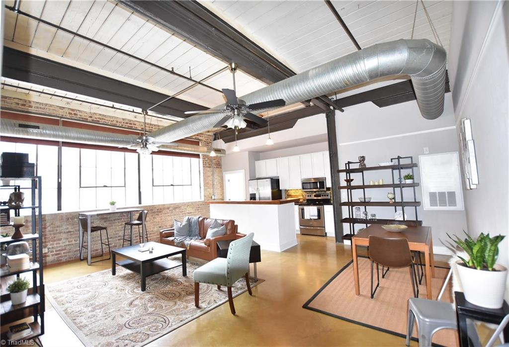Located in the heart of Innovation Quarter and Bailey Park! This corner unit loft has stunning views of downtown Winston Salem! Features an open floor plan with towering windows and natural sunlight,high ceilings with exposed ducts, rustic beams, brick walls and concrete flooring. Building amenities include secured parking, a fitness center with sauna, rooftop deck with skyline views, back patio with convenient access to the Greenway and common areas. Historical designation creates a reduction of taxes.