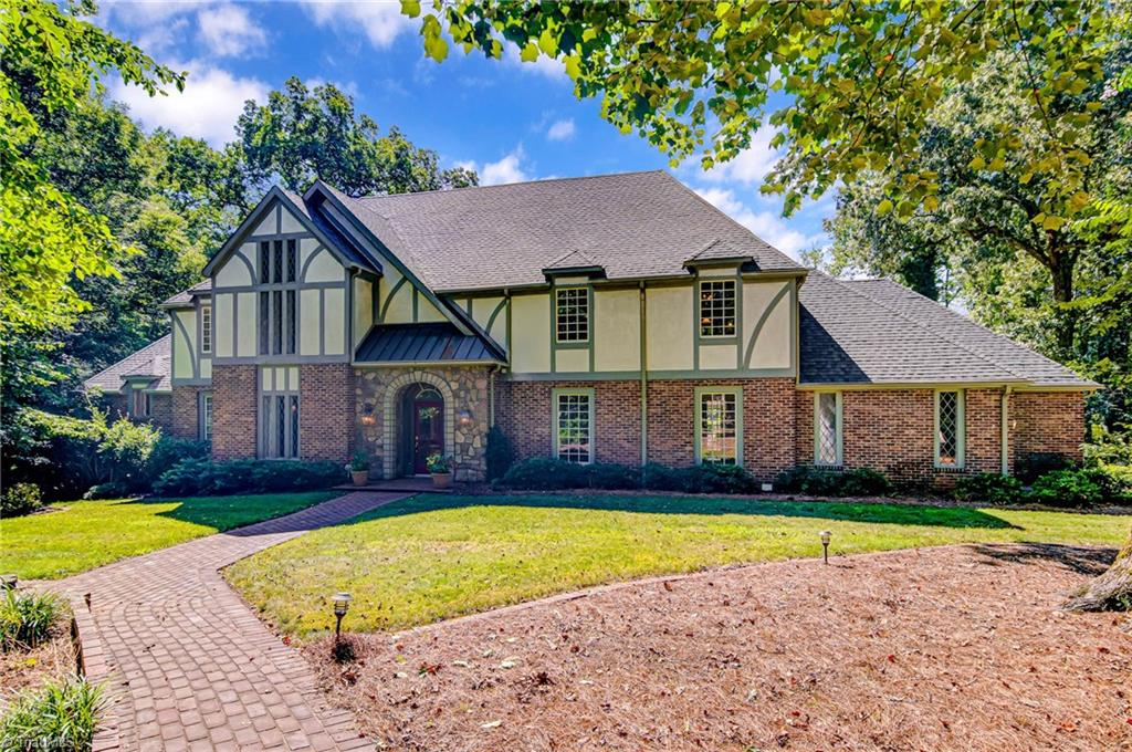 Stately Tudor in prestigious enclave within Reynolda Woods. The exclusive location provides much privacy. Nestled on 1+ acres of lushly wooded grounds, this fine in-town estate offers the best of indoor and outdoor living. Stunning craftsmanship in both the formal and informal areas; main level owners suite w/fpl; office; 4 upper level bedrooms w/bonus rm. Lower level exercise room. Covered brick veranda overlooks in-ground pool. Entertain in style in this relaxed & elegant atmosphere.