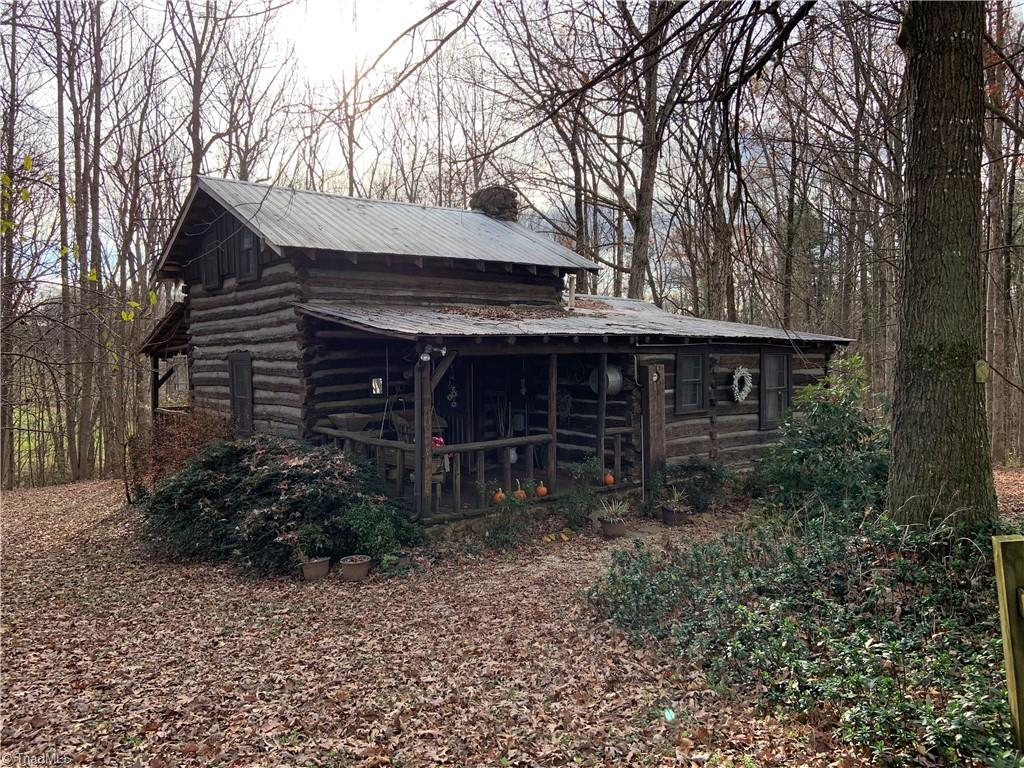 Enjoy privacy in this true log cabin on  3.3 acres with creek. Income potential. Home features rock fireplace in living room and wood cook stove in kitchen. New counter tops, hardwood floors. Heat pump. Small washer with wire dryer. Main level with open living kitchen dining area and bedroom with bath. UL large room big enough for two full size beds and bath shower only. Covered front porch with swing overlooking woods and creek below. Smaller cabin does not have heat or water but is used during warmer months. Features wood stove and wall air. Both cabins were recently treated outside with Thompson Water Seal.  High clearance vehicle recommended. No drive bys please home is in airbnb for remainder of year.
