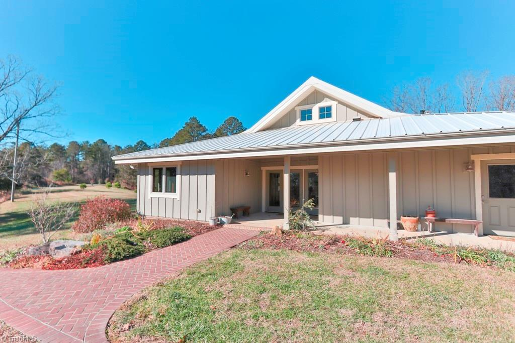"""5 Star Plus Home Energy Rating was achieved with SIP Construction. Structural Insulated Panels provide 7"""" insulation in walls and 12"""" in ceilings. Set on a spacious 8.5 acre tract surrounded by trees and a bold creek. The cleared acreage features a circle drive, 42 x 42 Morton Barn, 2 Koi ponds, raised garden beds and extensive landscaping around the property. A geothermal heat pump provides the home with radiant floor heating and forced air cooling. Exterior finish is Hardiboard with posts, beams and fascia of cedar and features a metal roof. Open floor plan in living area with vaulted ceiling. Kitchen cabinets are solid cherry and countertops are Corian. Bosch refrigerator and stove top are new in 2020. Bedroom and Bathroom doors are 36"""" wide.  Four skylights with 2 operated by remote control and with rain sensors. Covered patio is perfect for watching the wildlife and enjoying the garden beauty as the thousands of bulbs and hundreds of perennials put on a show throughout the year."""