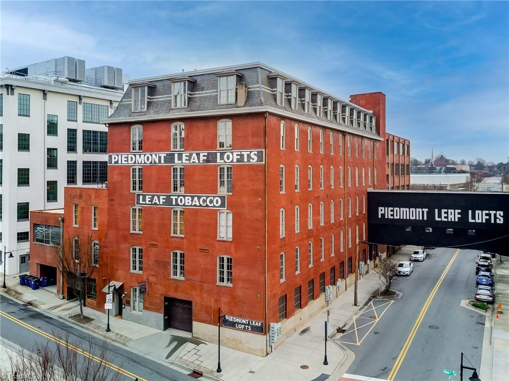 Rare offering in the heart of the Innovation Quarter, steps away from Bailey Park, the Long Branch Trail & WFU Medical School. 2-story penthouse condo with original floors, exposed brick, steel windows, tall ceilings AND PRIVATE ROOF TOP PATIO. 2 BR (with optional  3RD BR)/2BA with 2 parking spaces ,2 storage spaces, and building amenities (gym & add'l outdoor entertaining spaces). Recent mechanical upgrades.  Low property taxes (Historic Tax credit) off set HOA dues.