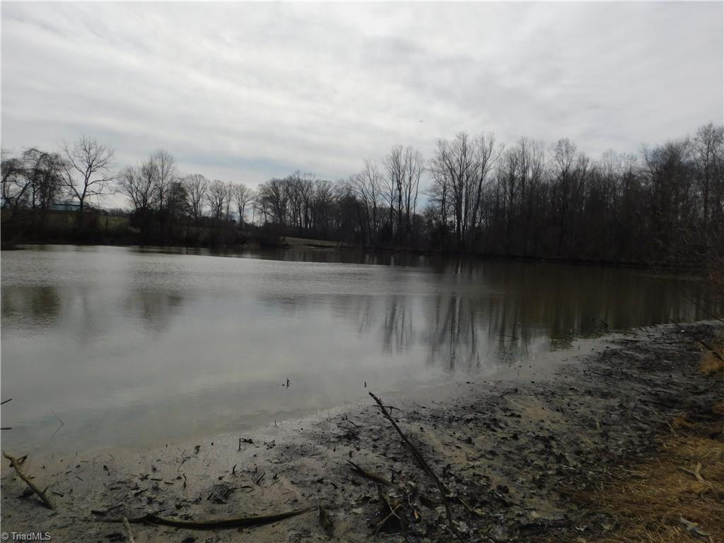 12.26 acres with deeded drive on rural low traveled road. Back border is a bold creek. Property line goes through a large pond so fish all you want.  Beautiful laying land with 3 old timey tobacco barns. Country living at its best.