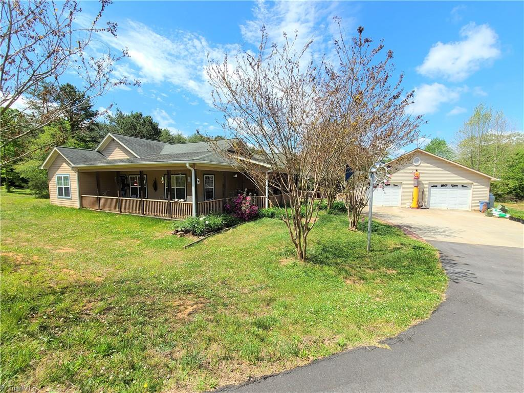 We have multiple offers. Highest and best due by noon on 5/13 Beautiful 2200 sqft 3 bed/2.5bath home w/basement on over 20 acres with spring fed pond.  Home has hard woods in living room, den and master, large living room and kitchen, split floor plan, covered porch on most of the home, detached garage, brand new 32KW Generac generator that will run the entire property,  paved private drive, spring fed pond, 30x30 covered open storage building, numerous other storage buidlings, tractor shed and completely surrounded by trees for complete privacy.  Lots of privacy with room to roam, yet within 5 minutes to US 52.