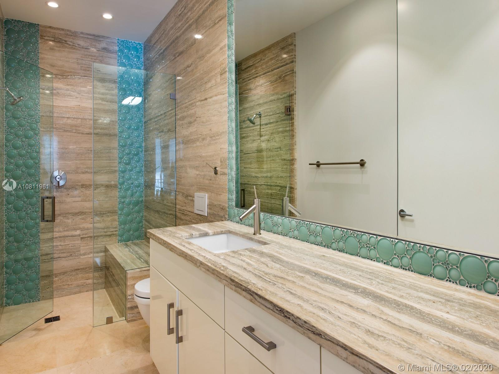 En-suite bathroom with marble countertops and floors.