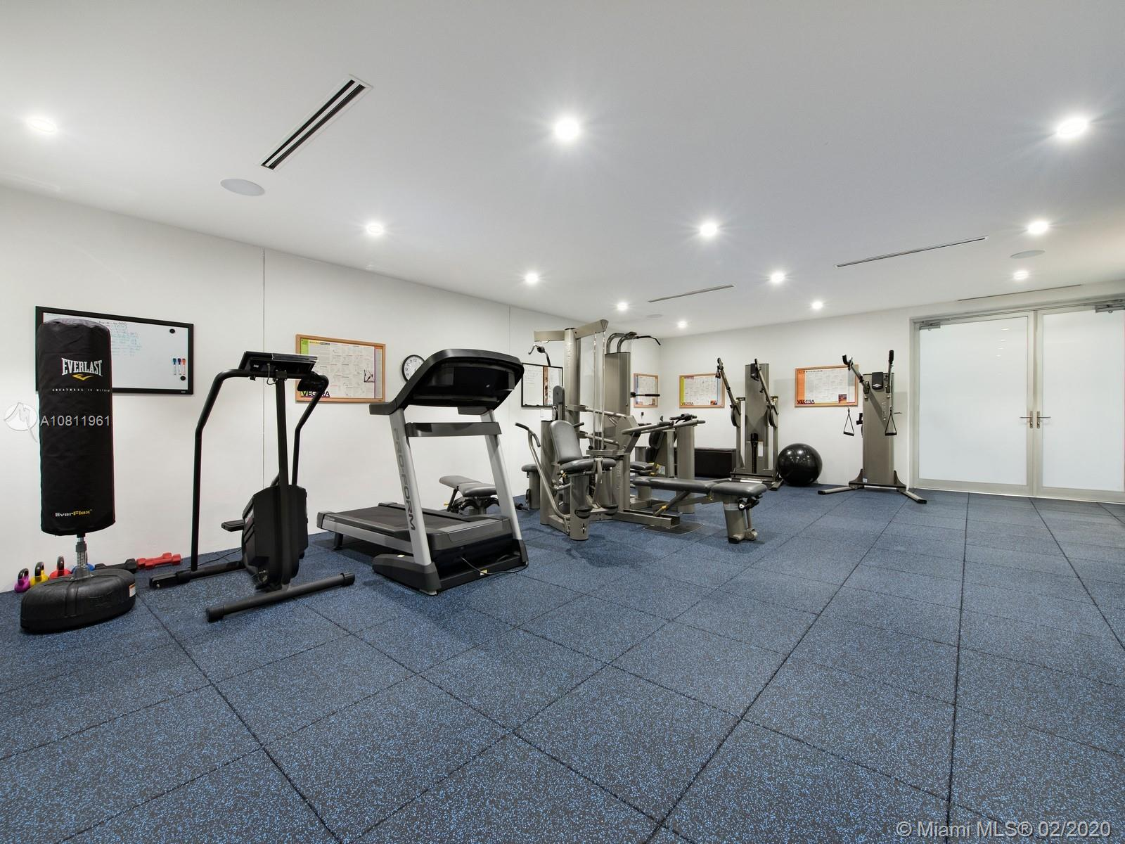 Gym with direct ocean views and NanaWall folding glass doors.