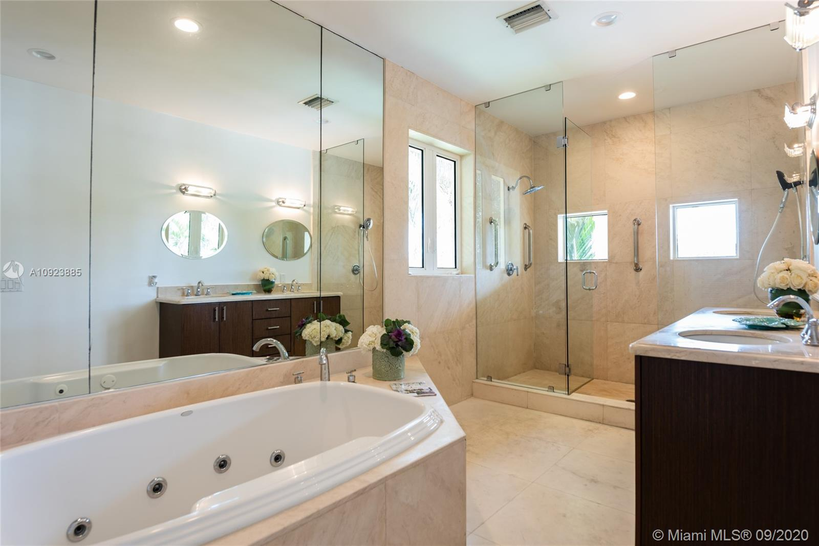 Large primary bathroom with spa tub and dual sinks