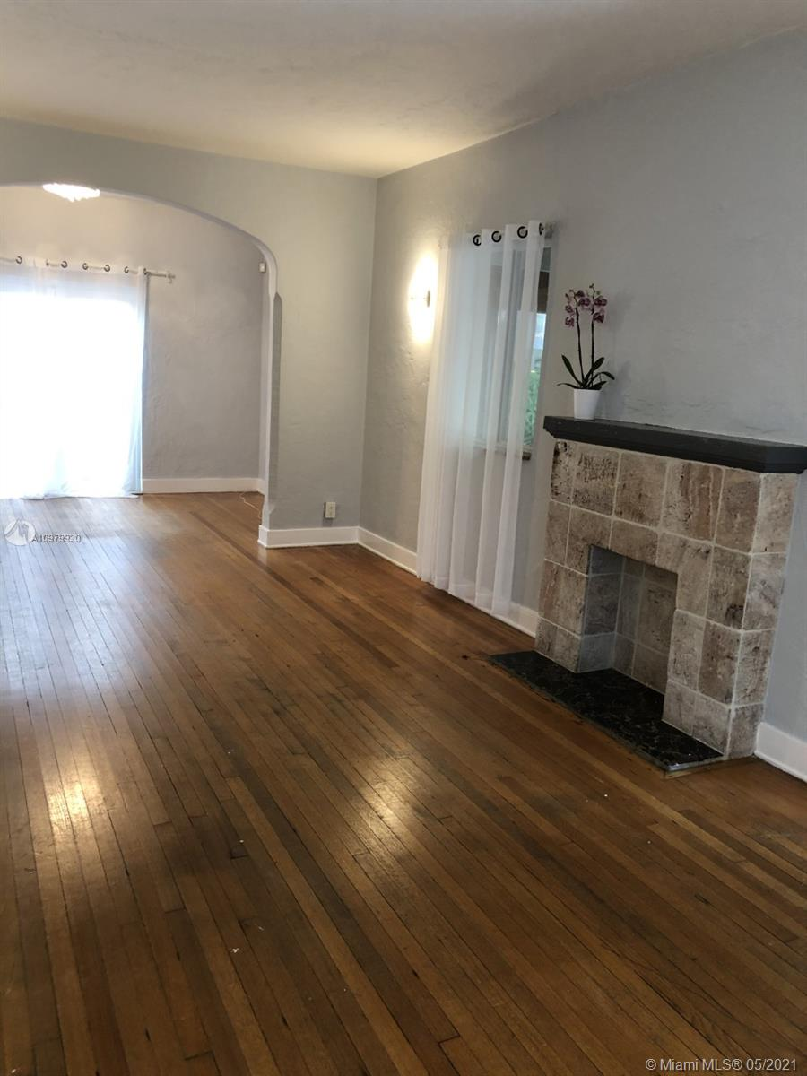 Side View of Living Room with Original Fireplace and Access to Covered / Screened-In Patio