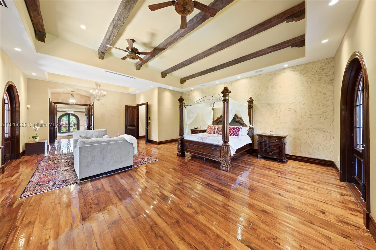 ANOTHER VIEW OF MASTER.. THE  FLOORING IS RECLAIMED WALNUT OLD WORLD PLANK STYLE.. VENETIAN PLASTER WALLS WITH BEAM DETAIL CEILING. THE FAR DOOR OPENS TO EXTERIOR STAIRWELL THE OTHER TO A FICUS REPENS LINED TERRACE OVERLOOKING THE WATERFALLS AND COCONUT PLANTATION