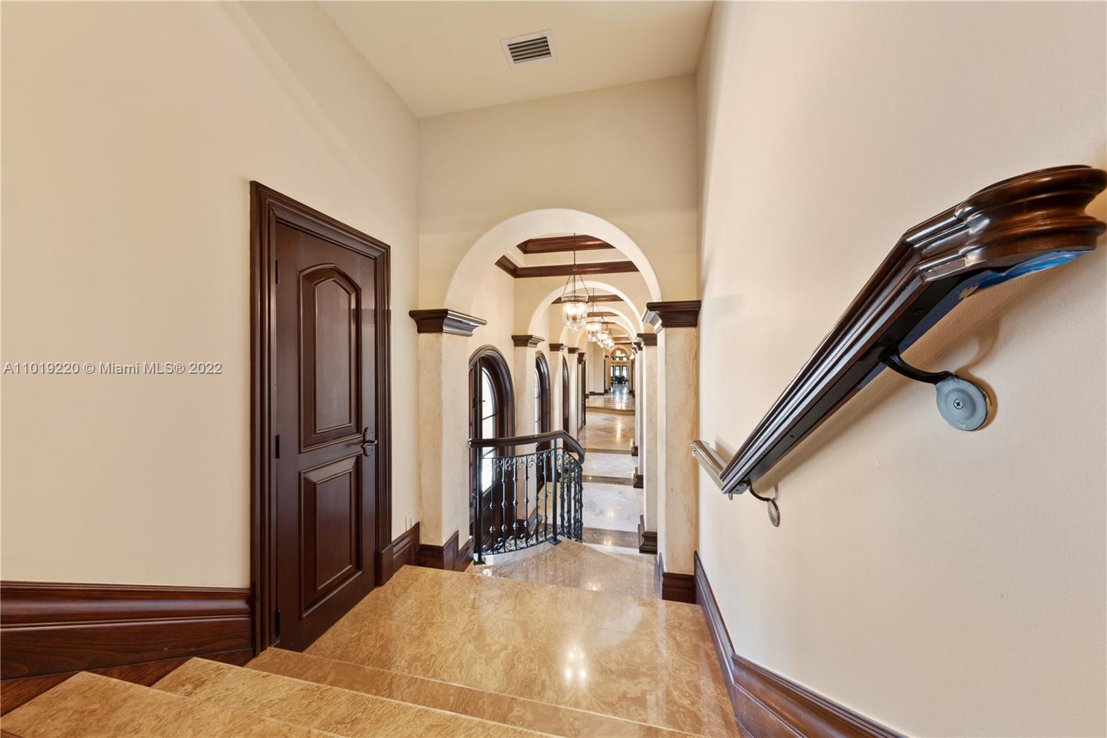 LEAVING MASTER  WITH A VIEW OF HALLWAY..THE MAHOGANY DOOR OPENS TO GYM, PLUS.