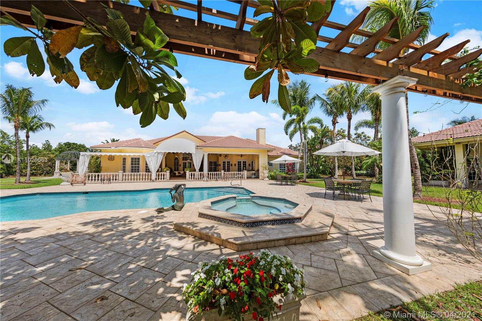 REAR VIEW OF THE MAIN RESIDENCE WITH A PARTIAL POOL HOUSE VIEW. THIS PLACE IS SET UP FOR ENTERTAINING...OR BRING THE ENTOURAGE AND ENJOY THE PEACE, QUIET AND PRIVACY OF THIS RESORT LEVEL HOME