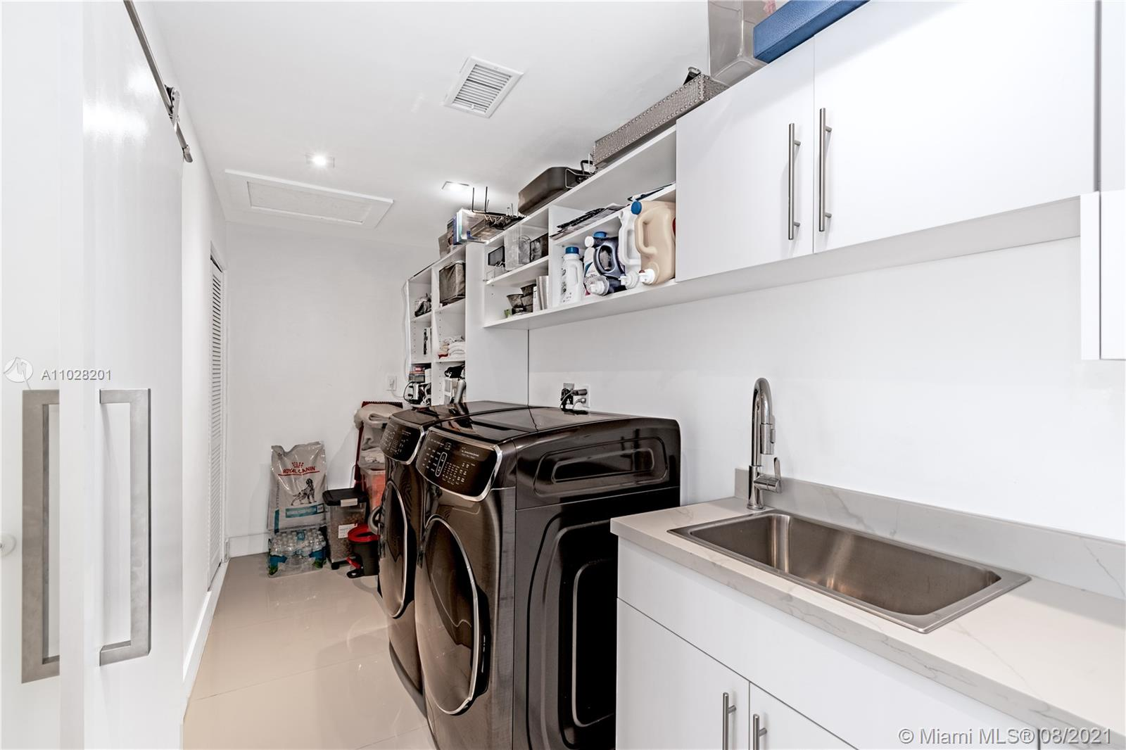 Large Laundry room with front smart technology Samsung front loaders and plenty of storage space.