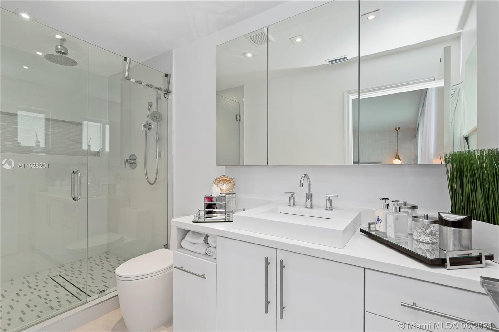 Gorgeous master bathroom with frameless shower door and rain shower.