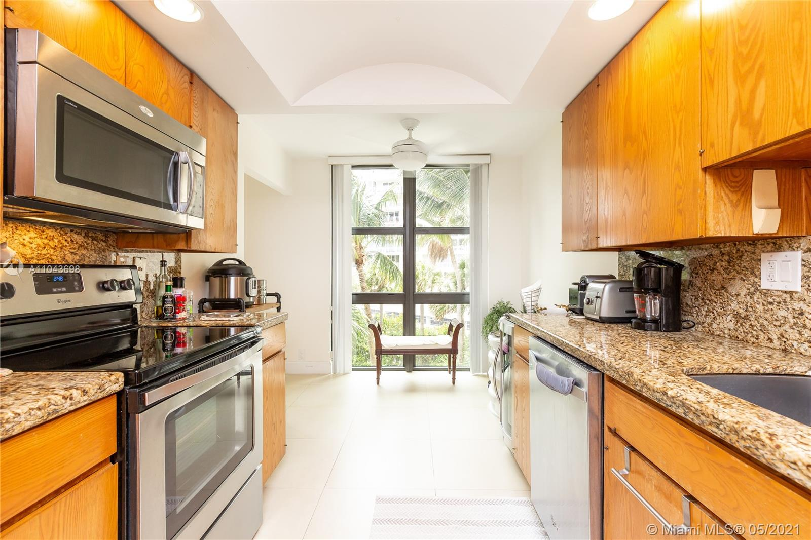 Kitchen features granite tops, wood cabinets and stainless steel appliances