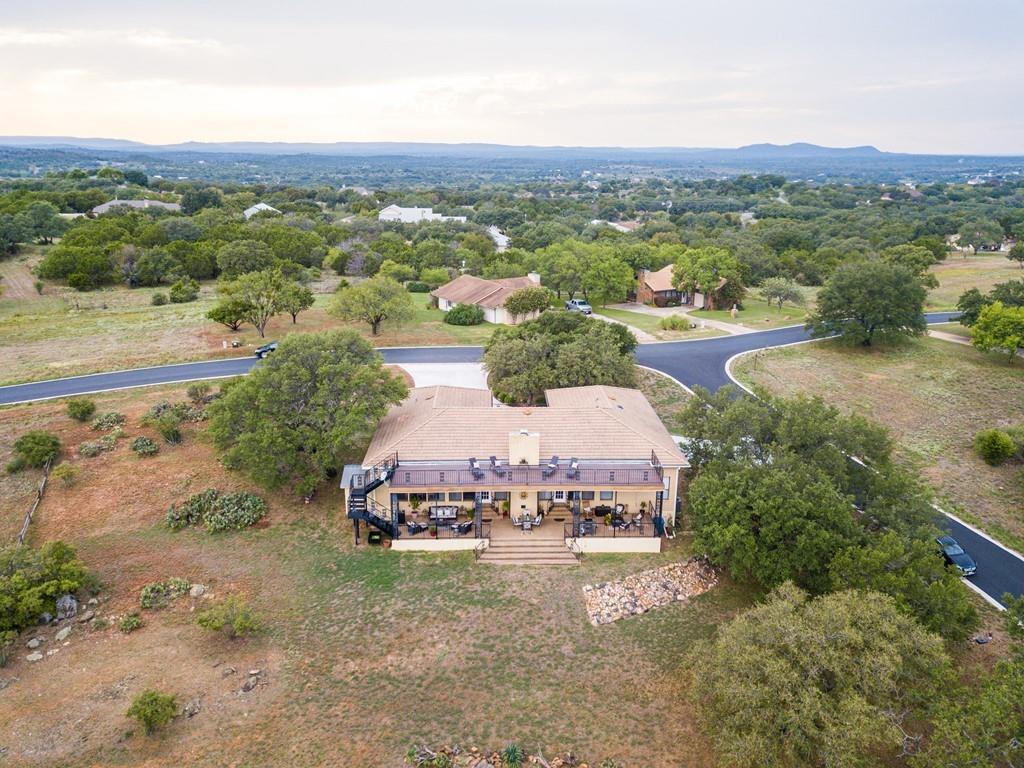 Horseshoe Bay's breathtaking Hill Country Views look eastward, across distant hills to magnificent Lake LBJ. The open floor plan, cathedral beamed ceilings, neutral colors, and impeccable design make the home's value apparent the moment you step inside. Embers glow from the living room fireplace while picture windows frame awe-inspiring vistas, protected by three conveying lots. Spend evenings on the spacious back covered patio, then move onto the upper balcony to take in the views and enjoy your personal Hill Country oasis.