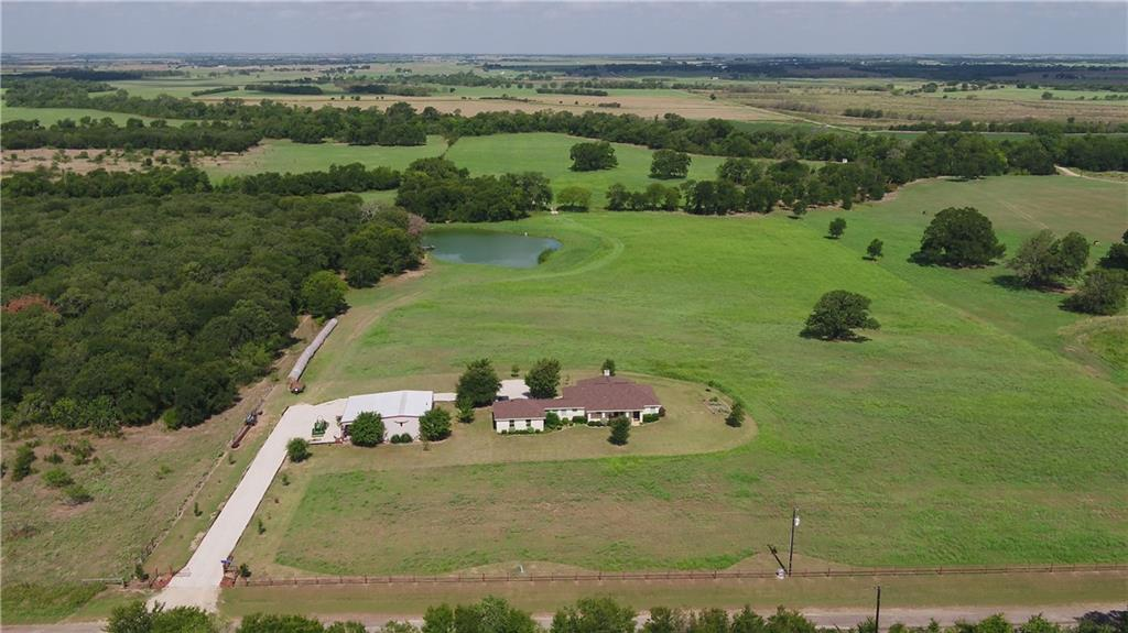 Awesome property with live-water frontage! This 37.79 acres tract is located just 33 miles from the I-35 corridor.  A custom, 1800 square foot, 3 bed/2 bath rock home sits near the front of the property and overlooks lush hay fields, pond and large trees. This home features a sun room, spacious living area, nice kitchen and 3 bedrooms. Tile floors throughout the home with carpet in the bedrooms. The living area has a double-sided fireplace and tall ceilings. The back porch has a covered outdoor kitchen area, offering relaxing views while you grill. The home has an attached 2-car garage and ample parking in the rear of the home. Great landscaping skirts the home area along with many desirable trees.  A 30x40 shop with extra lean-to storage is also in place. It has spray foam insulation, fans, heater, bathroom, and a unique upgrade! This shop has ample room for working on projects, or storing tools and equipment in it. The lean-to area is great for a boat or camper. The area around the shop has been rocked in providing great access no matter the weather.  The property is very productive and several hundred round bales of hay are cut on it per year with up to four cuttings some years! Beautiful scattered large oaks, elms and giant pecan trees dot this area as well. A 3/4 acre pond is situated a few hundred yards from the home and offers big bass to catch, wooden dock and year-round enjoyment. This property is also great for hunting with lots of deer and hogs frequenting it.  The rear boundary of the property is bounded by approximately 1800' of Brushy Creek frontage. This creek offers year-round live water access and is a large creek for the area. A small cabin and bath-house sit along the creek's edge giving you a great shady spot to spend the weekends or invite guests to. The cabin has power, septic, RV hookups, and an A/C and heat unit. A fire pit is located between the cabin and bathhouse, making it a great place to sit and relax.