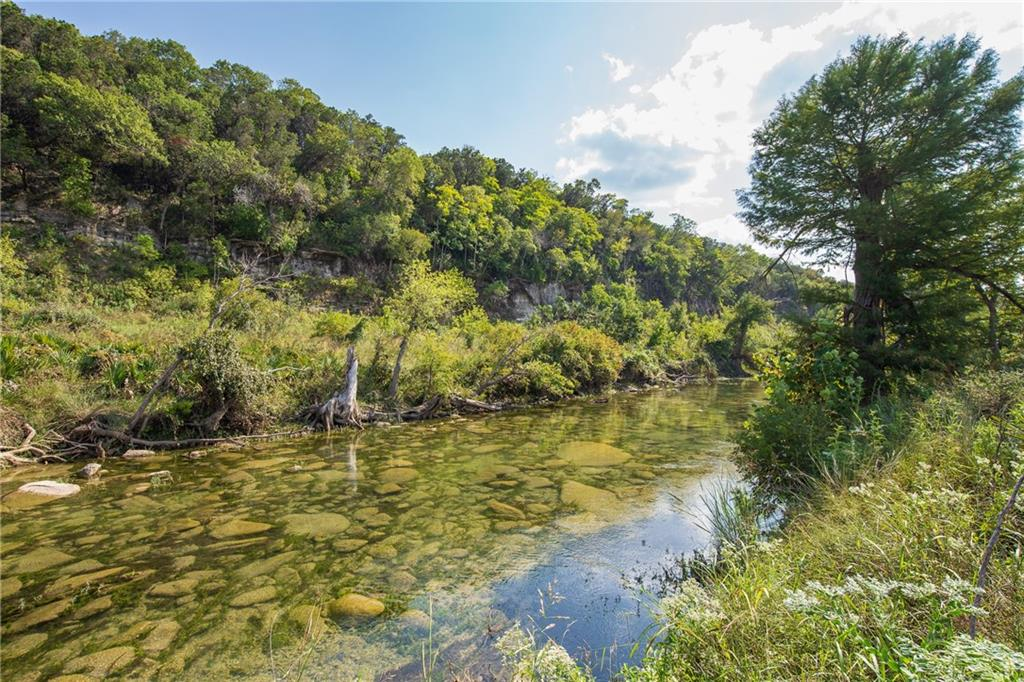 Gorgeous Waterfront Acreage in Wimberley.  This one of a kind property offers 14+/- acres and 1300+/- feet of Blanco River Frontage. The waterfront is very private, lined with Cypress trees, and looks across to a scenic bluff. UNRESTRICTED and has an ag valuation for low taxes. Great potential for an income property. You won't find this much river frontage anywhere else in Wimberley. The top portion of the property is level, cleared, and fenced. Existing well on site. Incredible opportunity to own your own piece of the Hill Country!
