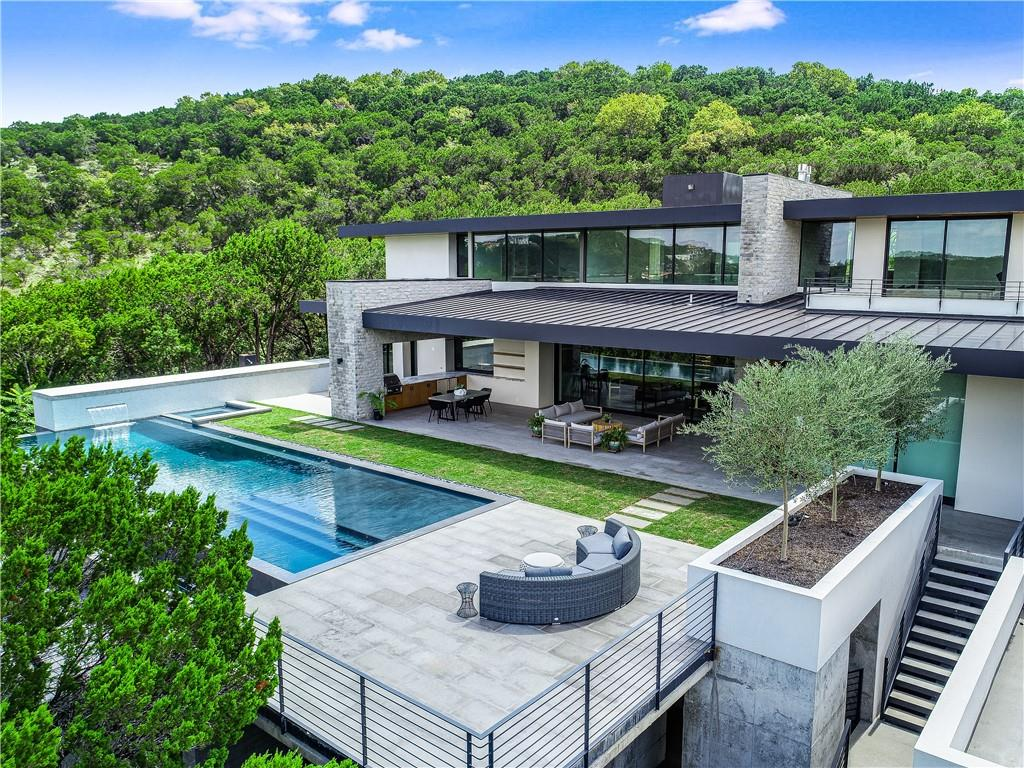 """The Sweet Sky Residence. Located in the heart of Westlake Hills and surrounded by some of Austin's finest architecture, this house represents one of the last Dick Clark hands-on designs before his passing in 2017. Renowned Austin architect Dick Clark is often referred to as the Godfather of contemporary design. This home is designed on two levels, in a linear """"L"""" shape to allow the main spaces to spread out more evenly across the site in the natural direction of the topography.  The result is a house built """"into"""" the hillside with views maximized off the back patio facing conservation land and canyons. The pool was built substantially out of grade and allows a secret subterranean passageway to yoga, zen and play spaces nestled below the pool and into the trees. Every detail in this home was meticulously planned to perfection from the cantilever staircase to heated bathroom floors. Exquisite details and luxurious finishes at every turn. The Juniper Ridge development consists of six private lots on a cul-de-sac street with the Sweet Sky Residence consisting of 2 private acres, surrounded by 5 acre greenbelt and 32 acre conservation preserve."""