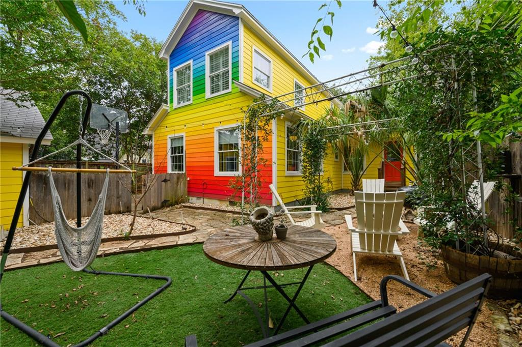 """An eye-catching rainbow wall is a nod to the legendary flair of San Francisco's colorful homes in The Haight, known as the """"Painted Ladies."""" The wall was painted in the spirit of unity and to add a sense of fun and whimsy to the backyard. Always a conversation starter! The property includes the bright and beautiful 3/2 main home plus a detached 1/1 Zen retreat-style guest house. Each dwelling has a separate outdoor entertaining area. The main home features wood floors, an open living plan, dual pane energy efficient windows with elegant plantation shutters. Bright dining and living rooms open to the kitchen with breakfast bar, which is a great place for entertaining or helping kids with homework. 2 beds, a full bath and a laundry facility are off the kitchen/living on the main level and look onto the backyard. The primary suite is the entire upstairs: airy bedroom with plenty of windows looking out into treetops. An open office area is at top of the stairs. The spacious primary bathroom includes 2 sinks, a clawfoot tub, and walk-in shower, custom tiles and a stained glass accent. Separate 1/1 guest house or rental is also open floor plan with a full kitchen, living room with Murphy bed, a full bath with walk-in shower, and a spacious bedroom that accommodates a king-size bed, dressing area, and has second entry. Location is walkable to acclaimed Bryker Woods Elementary, shopping, markets, and many restaurants that range from fast food to fine dining. Walk to Brick Oven Pizza and have a glass of wine while you wait for your pie. Or check out nearby Ramsey Neighborhood Park with a playground, outdoor pool, tennis & basketball courts & a softball field. If you're a cyclist, you'll enjoy the network of urban bike trails. With quick access to both Mopac and Lamar, this property really checks all the boxes."""