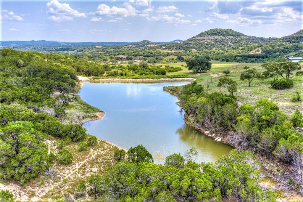 A Texas gem, 23.5 acres of spectacular Hill Country views nestled in the beautiful Ranches of Brushy Top.  Mature live oak, red oak, redbud, ash juniper, and madrone trees dot the landscape.  Enjoy your own private 1.3 acre Pond stocked with Florida bass, bluegill, redear and shad.  Diverse scenery and elevation, including native-grass pastures, wooded hillsides, and rocky mountaintops.  Just 45 minutes from Austin and San Antonio, this unique property offers multiple build sites, each with breathtaking views.   Leave the stress of the city behind.  Design and build the home of your dreams on this incredible piece of property.
