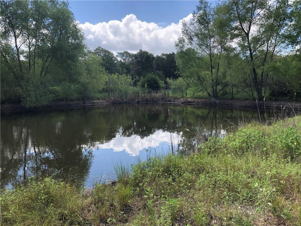 28.9 acres - just the right size for enjoying the great outdoors about 1.5 hours from Houston or an hour from Austin. Beautiful property is very private with a 60 foot wide entrance that leads back to a lovely pond, then opens out to heavily wooded acreage with some clearings and trails. Well fenced on three sides, partially fenced remaining side. Plenty of cover for wildlife. Preferred mix of hardwood and evergreens. Adjoining large tracts. This property is already platted in two tracts so easy for a family to share with 30 feet of road frontage for each tract. Seller wants to sell together. Only restriction per seller is 25 foot building set back from property lines. Adjoining 58 acres acres also for sale.
