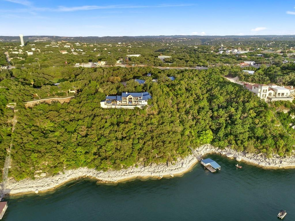 Rare generational estate setting on Lake Travis comprised of just under 8 acres. Approximately 600ft of main body frontage on deep water. Spectacular sunset water views from across the entire property. Unique main house built in 1994 with potential to be something special again. Architecture by Barley/Pfeiffer. Included are 2 guest houses and multiple structures/improvements throughout the property. Property is not zoned and can be subdivided, development possibilities too. Survey along with tree/topo available. Full list of improvements/details below: