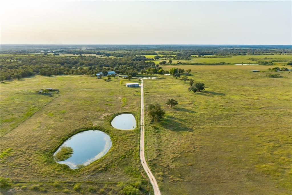 This property is a 155.951 game fenced acreage with paved road frontage. 8 foot game fence encloses the property with cross fences/automatic gate opener at entrance. Nice combination of wooded areas for hunting, clean hay fields, and grazing pastures. Easy 30 minute commute to Austin. Includes two homes: Main barn dominium is 1500 square foot 2 bedroom/2 bath/concrete floors with an additional 900 square foot room with full bath upstairs within a 6,000 square foot barn with concrete slab/3 roll up doors/and nice spacious porch to watch the gorgeous sunset. Metal roof and walls for low maintenance. Covered hay storage.  Mother-in-Law barn dominium -within walking distance of main home but not too close - 2,600 square foot under roof with 1 bedroom/2 bath/concrete floors (1,035 sq ft living area/547.5 covered porch/1,012.5 sq ft tractor/UTV/auto garage with 3 roll up doors(one automatic). Metal roof and walls for low maintenance.  Utility shed, dog/goat/chicken fenced areas. Covered equipment open air pole barn. Working cattle pens with power and water to the pens/includes covered squeeze chute. Irrigated field/5ponds/2 wells (one is a Plum Creek Water Conservation permitted well) This property is a MUST SEE!  Schedule an appointment today/listing agent must be present at all showings. Property Aerial Video under the Tour Tab in the upper right corner that captures the beauty of this property!