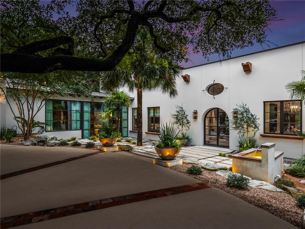 This Santa Barbara style home is situated above Bee Creek on Lake Austin. Gated and walled from the street, the private setting offers the perfect retreat only minutes from downtown. Recently updated, the home is centered around a beautiful courtyard with water feature and Jasmine vines. The gracious proportions of the floor plan make the property ideal for large scale entertaining, yet still feels cozy for everyday living. The outdoor spaces offer several covered terraces, a lap pool and outdoor dining area with kitchen and fireplace all surrounded by tree top views. Steps below is a fantastic boat slip with screened porch above and a stone fire pit. SQFT per floorpan graphics, lot size per TCAD.