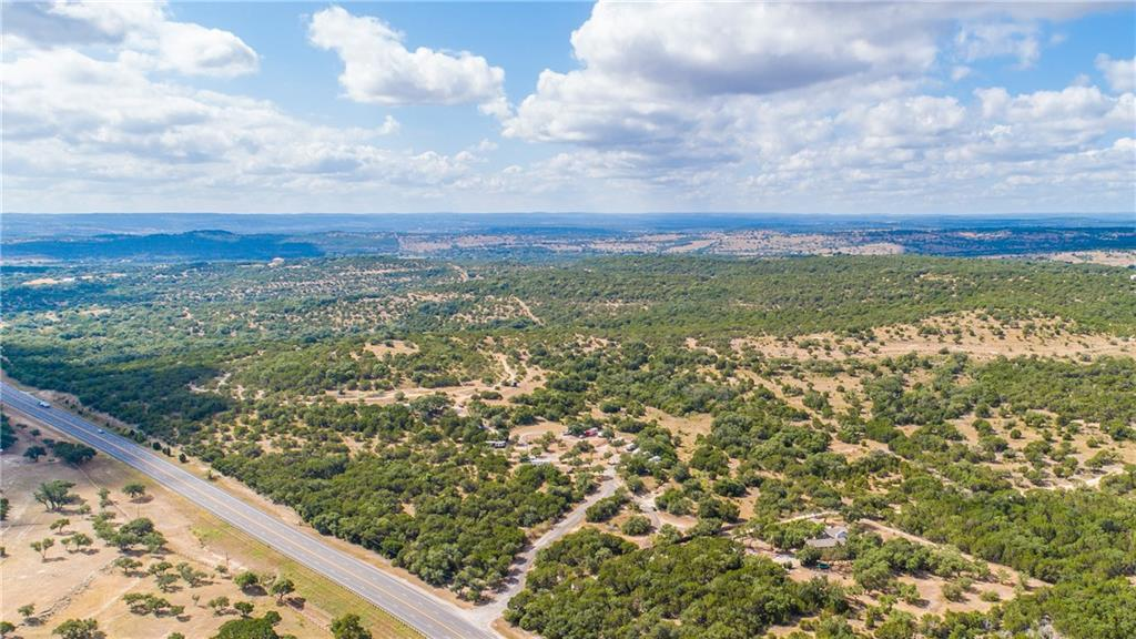 Beautiful wooded land on Highway 71 in Spicewood, Tx with fantastic building sites with 360 degree panorama hill country views.  Currently part of the land is being used as RV Park with 16 spaces available.  All mostly full, long time tenants, and all month to month.  There are 5 wells, 5000 gal holding tank, 2 septic tanks, electricity to highest elevation, and 2 entrances off of 71 Highway.  Small house has 2 rooms, bath, plumbed for kitchenette, porch, & covered patio area.  Could be developed into a larger RV park, mobile homes, or subdivided.  Call agent for more details.