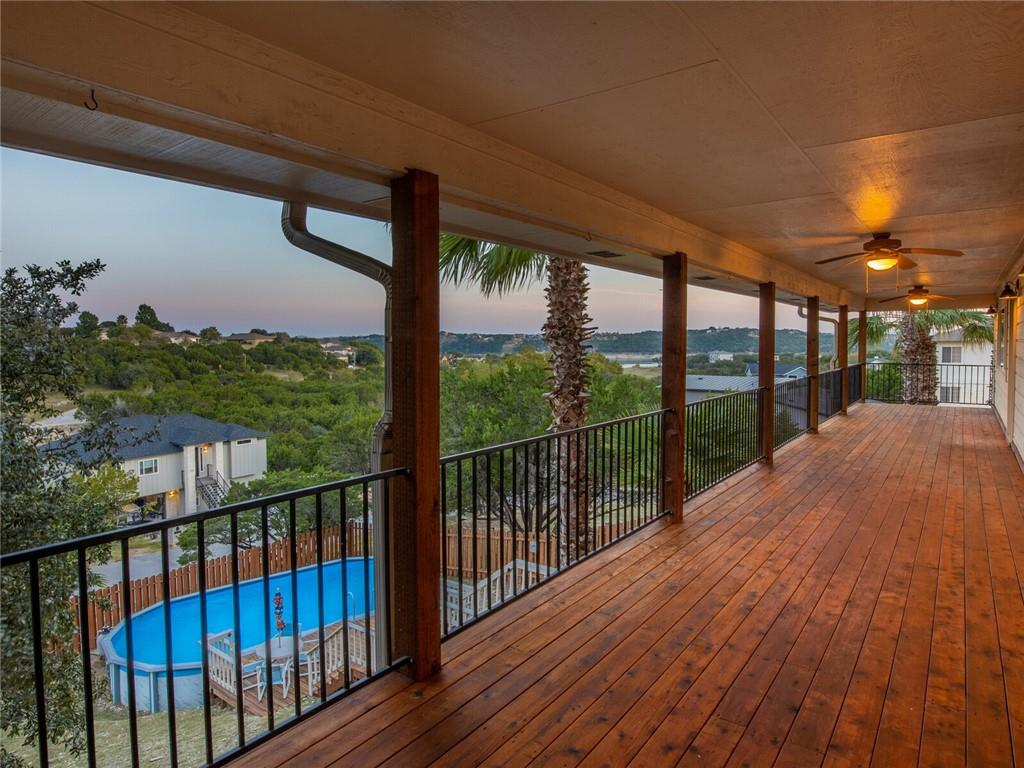 Feel like the king of the hill in this spacious corner lot home with views of Lake Travis, the golf course, and the Texas Hill Country from two covered decks. Situated on 3 cul-de-sac lots totaling .714 acres, it has an above ground pool in immaculate shape with extensive decking, as well as a sports court. It's your own private playground! But you're also within walking distance of 2 private gated parks with boat ramps and fishing docks on Lake Travis. The updated gourmet kitchen features custom cabinets and a subzero refrigerator. Other great features of the home include top end Carrier & Bryant air conditioning systems with wifi and humidity control 16 SEER two-stage heat pump, a small study, a cedar-lined closet, 3 spacious bedrooms with HUGE walk-in closets, an air-conditioned workshop, and lots of storage.