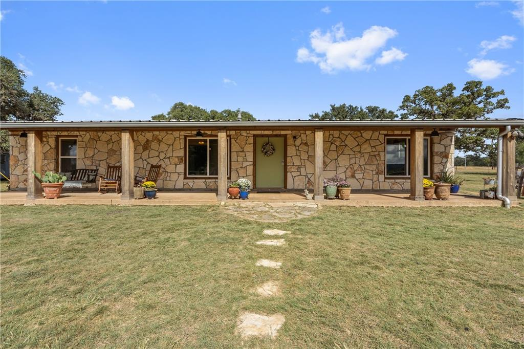 This 62.5 acre property is a horseman's dream offering everything you need and want in a ranch. As you enter the property, you're surrounded by manicured grounds and large oaks that open up towards the house, yard, and horse barn. The 4 bed/4 bath rock home is +/-1800 square feet finished with a cozy farmhouse feel. The living area is open to the kitchen, and each bedroom hosts it's own bathroom. The front porch extends the entire length of the home, and makes for the perfect place for morning coffee with amazing views. Outside the yard and adjacent to the house, you will find the firepit area and 4 stall horse barn with a finished office inside. The stalls are large with attached runs for plenty of room for the horses. On the back side of the barn is the riding area that can be easily converted to a roping or covered arena. The riding area overlooks the most gorgeous rolling field you have ever seen. After driving through the field, you will come to a wooded area that makes for terrific hunting with whitetail and axis being plentiful. There is a small stock tank on the property that holds about 4' of water consistently. With nothing but hilltops in view, you feel secluded from the rest of the world.