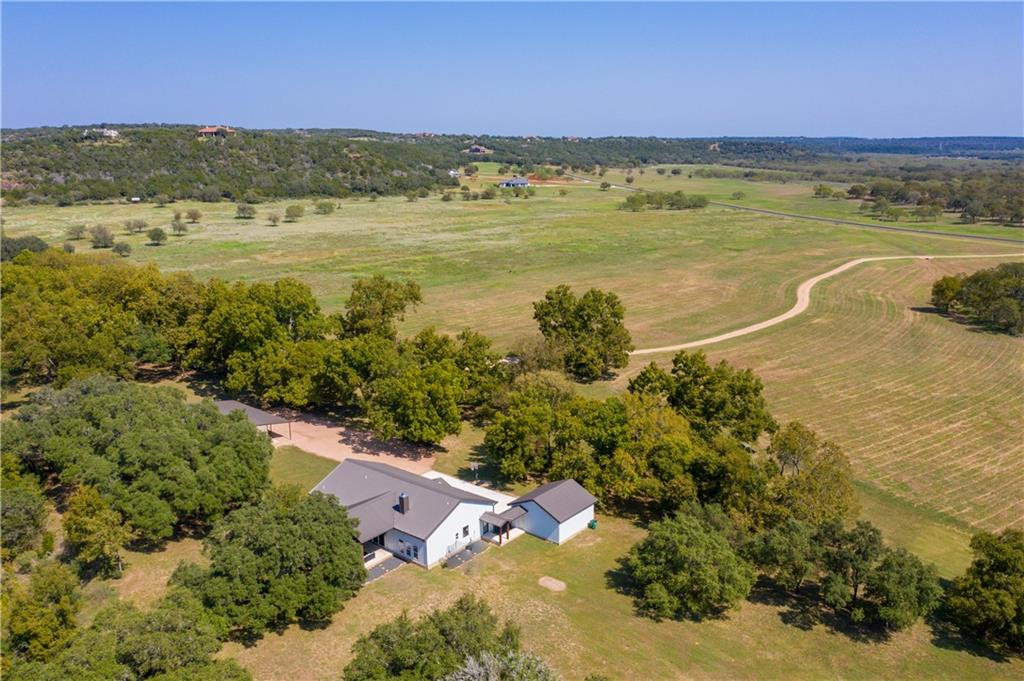 Escape to the hll country on this nearly 25 acre hideaway in beautiful Marble Falls. This contemporary farmhouse offers 4 bedrooms, 3 full baths plus study with large bunk/gameroom upstairs.  The huge kitchen island, open concept and outdoor living/cooking space are perfect for large gatherings. Home features gorgeous stained concrete floors, large walk-in showers in all baths, covered back patio and walk-in pantry/wine grotto. Detached workshop/mancave has a separte downstairs 1 bedroom, 1bath apartment. Nestled amonst plentiful oaks and backing to Dry Branch creek in the gated community of Stone Mountain and located north of Marble Falls near several lakes and the incrediable ameniites of the hill country - golf, hiking, boating, fishing, wineries and more! Low tax rate and currently wildlife exempt.