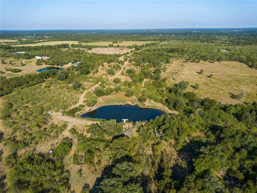 Beautiful land with 1 pond and approximately 15 acres of improved pasture with Tipton grass! Only about 1/4 mile is gravel road.  Lots of beautiful building sites to choose from! Only 15 minutes to Bastrop HEB, etc. 25 mins to Tesla, Amazon, ABIA! Large oaks trees scattered around the property. Call to schedule your showing today!
