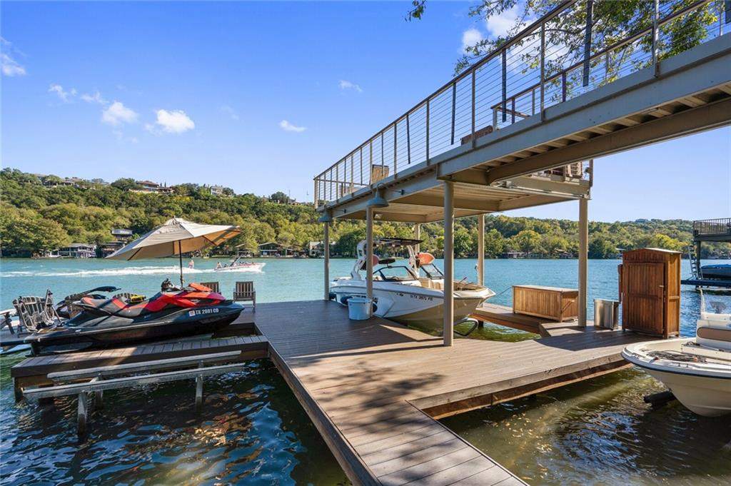 """Rare offering for this FAB Lake Austin Waterfront home with ~100 feet of frontage~Beautifully manicured, gently sloped and terraced lawn with room for a pool. With recently rebuilt piers, the coveted 35', two-story, double slip boat dock with party deck upstairs accommodates a variety of watercraft. A new bulkhead with beach entry has been permitted and designed and will make this slice of heaven even more enjoyable.  The charming cottage was lovingly renovated from """"head to toe"""" and is casually comfortable with a covered deck and patios to entertain effortlessly in rain or shine. The substantial cosmetic updates throughout are chic, and the home's systems have also been updated including HVAC, electrical, a smart TRANE thermostat, surround sound and more. From the moment you enter the property's privacy gate, you will be enchanted with magical Lake Austin as the backdrop of every room."""