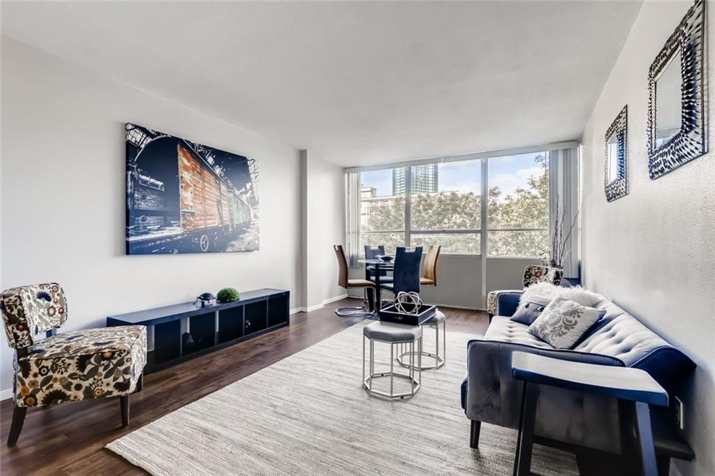 This condo has a spacious living area, lots of natural light and views of tree tops and the UT Tower.